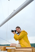 A Male Captain In A Yellow Raincoat On A White Yacht