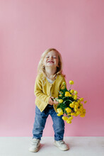 Happy Little Child With Bouquet Of Yellow Buttercups On Pink Background