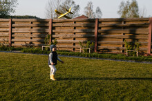 Happy Boy Playing With Plane In Yard