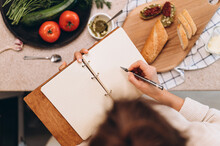 Anonymous Woman Drawing Bruschettas In Notebook