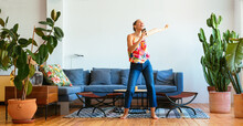 Positive Woman With Smartphone Dancing At Home