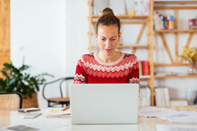 Focused Woman Using Laptop In Home Office