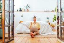Cheerful Woman Watching Movie On Laptop In Bedroom