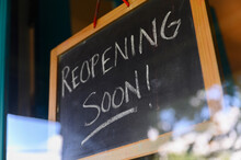 """Reopening Soon"""""""" Sign Hanging In Small Business Window"""