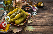 Pickled Cucumbers, Garlic And Bay Leaf On A Wooden Background.