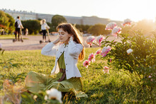 Young Female Sitting On Lawn With Blooming Peony In Public Place