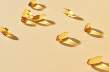 Omega-3 Vitamins, Fatty Acids. Fish Oil In Yellow Capsules On A Yellow Background.