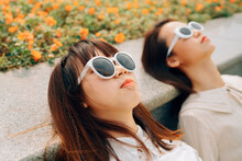 Two Young Women Lying In Flowers Enjoying The Sun
