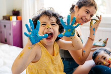 Mixed Race Child Showing Hands Covered In Paint