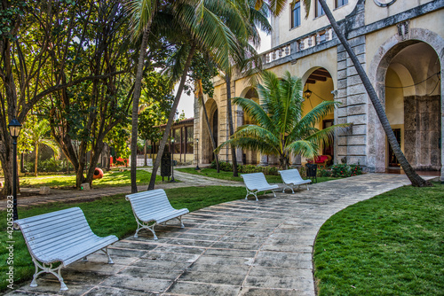 Photo Four white benches on a path to the entrance of a building in Cuba