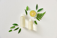 Essential Oil And Extract In Bottles, Fresh Herbs, Lemon Slices Copy Space.