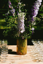 Yellow Vase With Green And Purple Flowers On A Wooden Table With Empty Champagne Glasses