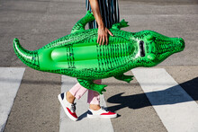Man With An Alligator-shaped Floaty On The Street