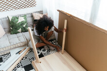 Positive Woman Assembling Table At Home