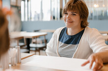 Happy Woman Sitting At Cafe Table