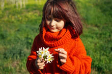 Young Girl Holding A Bunch Of Small White Flowers