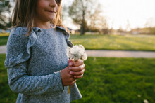 Girl Makes Wishes On Dandelion