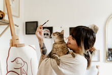Young Female Artist Painting On Her Studio Holding Cute Cat