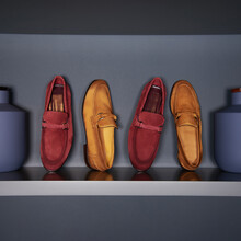 Four Colored Suede Shoes Lie On A Gray Background.