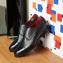 Handmade Black Patent Leather Shoes On A Wooden Chest Of Drawers