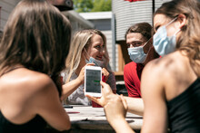 BBQ: Woman With Face Mask Uses Cell Phone Before Lunch