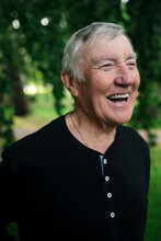 Older Man Smiling And Laughing Outside Near A Tree