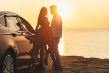 The Beautiful Couple Standing Near The Car On The Sea Shore