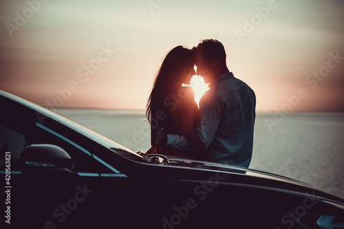Fototapeta The romantic couple standing near the car on the beautiful sunset background obraz