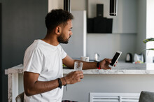 Black Man With Drink Using Smartphone In Kitchen
