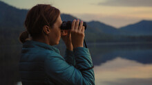 Portrait Of A Woman Who Looks Through Binoculars On The Shore Of A Mountain Lake In The Sunset, Silhouette.