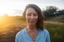 Deep Breathing, Content Mature Woman Portrait At Sunset