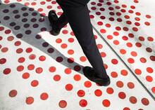 Elegant Man Walking On A Polka Dots Surface