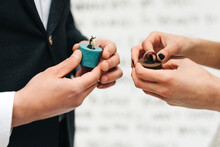 Bride And Groom Holding Wedding Rings And Holder At Ceremony