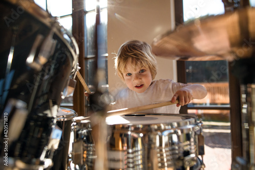 Canvas-taulu Front view of small boy indoors at home, playing drums.