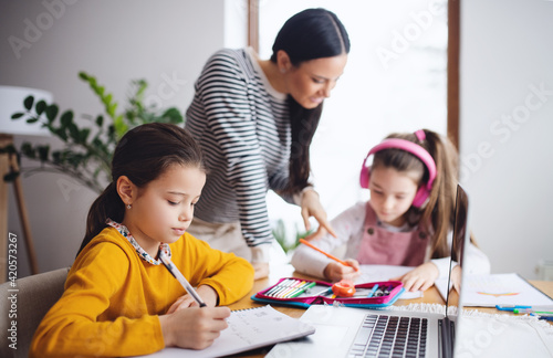 Mother with school girls indoors at home, distance learning and home office.