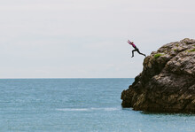 Teenage Girl Leaping From Rocks Into The Sea.