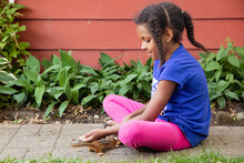 A Young Child Sitting In Front Of A Trail Of Peanuts While A Chipmunk Approaches