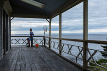 Young Boy Sitting Looking Out At Ocean From Porch In Maine
