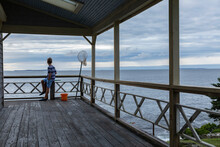 Young Boy Looking Out At Ocean From Porch In Maine