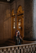 Woman Taking Pictures Inside Cathedral