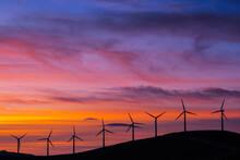 Wind Turbines In Purple And Orange Setting Sun