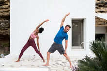 Diverse Couple Doing Yoga On Terrace Together