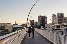 2 Young Woman Walking Across A Bridge In The Afternoon