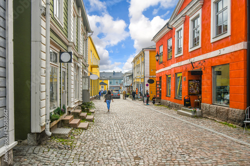 A woman walks down the main touristic street in the medieval village of Porvoo, Finland Fototapet