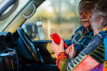 Senior Woman Showing Her Husband The Map On Her Mobile Phone