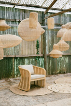Wicker Armchair Surrounded By Lamps
