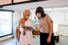 Coworkers Wearing Face Masks Using Tablet