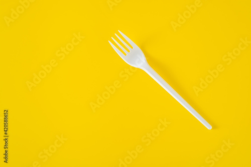 Fototapeta Plastic fork on yellow background. Picnic plastic disposable tableware, copy space obraz