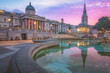 A vibrant colourful, dramatic sunrise or sunset sky at Trafalgar Square and the National Gallery in central London, UK.