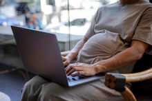 Pregnant Woman Working On A Computer From Outdoor Co-working Space